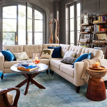 gray living room with white sofa and blue accent pillows