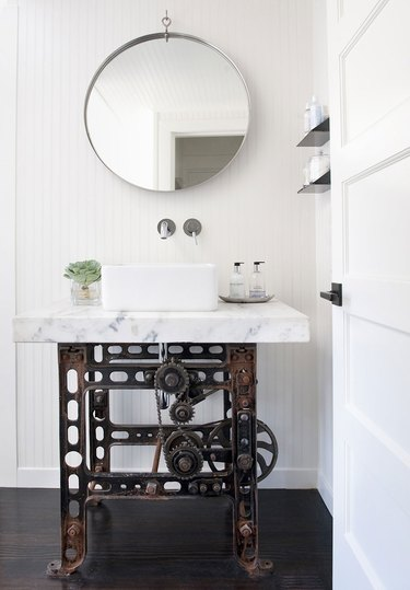 sculptural industrial bathroom vanity with Carrara marble top