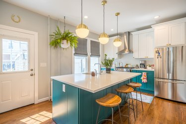 bright teal kitchen island with brass pendant lighting