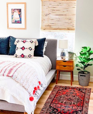 Bedroom with a range of textiles, including throw pillows and blankets, a red-dominant kilim-rug, and woven black and white planter.