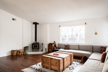 open living room with stove in the corner, hardwood floors, sectional couch