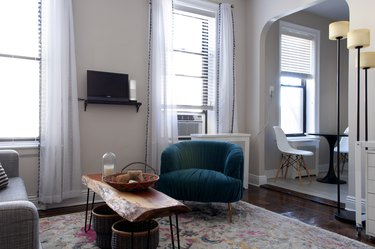 living room with white curtains, wooden table, and blue velvet chair