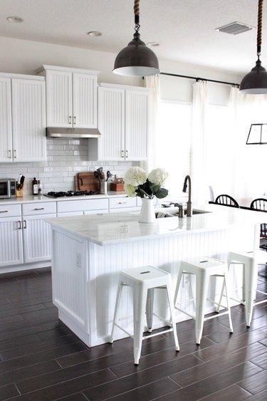 white beadboard kitchen island and white countertop