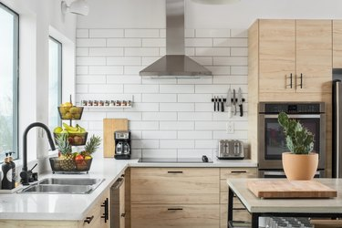corner of kitchen with light wood cabinetry, stove hood, white subway tile walls