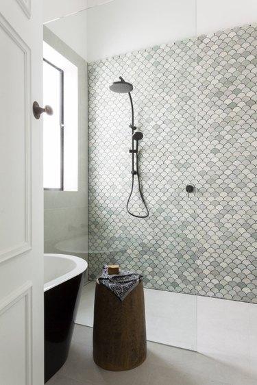 fan-shaped mosaic tile accent wall in green bathroom