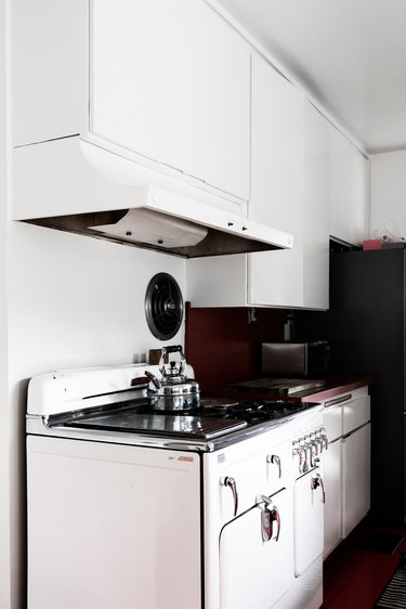 oven with range hood and white cabinets