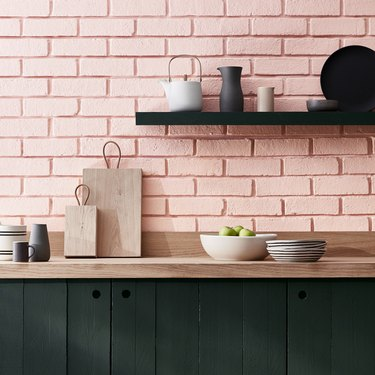 pink brick backsplash with wood countertop and open shelving