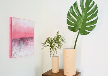 Leather vases holding monstera leaf and greenery