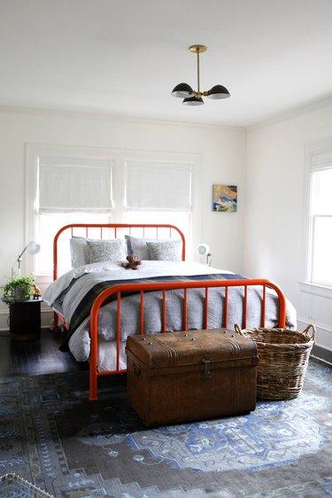 Midcentury-Style bedroom chandelier hanging above red bed frame