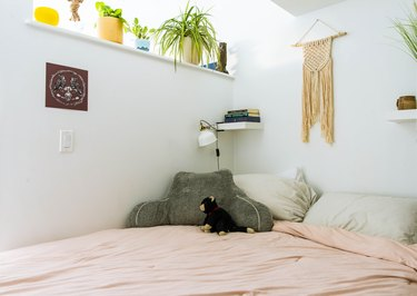 Bed with macrame hanging on wall
