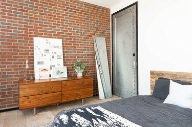 Bedroom with brick wall and industrial door