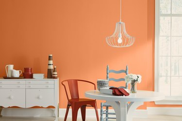 dining area with white hanging lampshade and orange wall