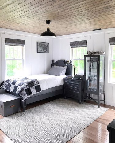 rustic bedroom lighting idea with wood plank ceiling with black and gray color palette