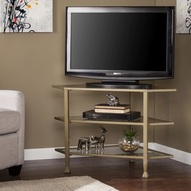 gold and glass corner TV unit with open shelving