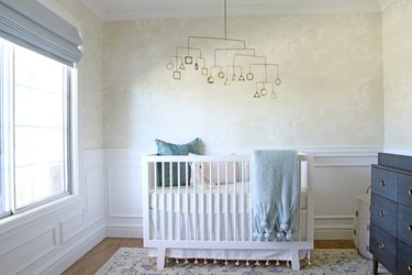 tan and blue nursery idea with mobile hanging above crib and wallpaper on walls
