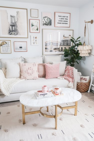 living room with pink pillows on sofa and pink blanket