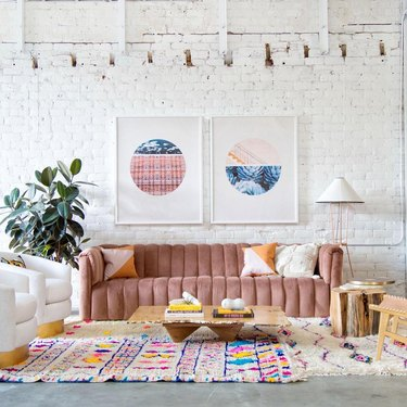 living room with pink channel-tufted sofa and pink accents