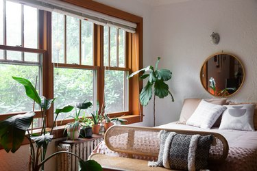 bedroom furniture idea with cane bench in front of bed with mirror and potted plants