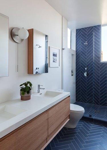 navy blue ceramic tile in herringbone pattern on bathroom wall and floor