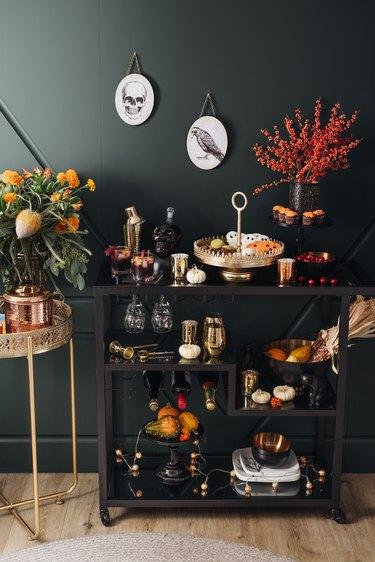 small fall pumpkins on black bar cart