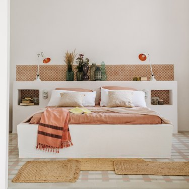 vases full of dried foliage lined up on a headboard
