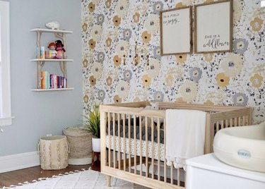 yellow nursery idea with floral accent wall and bluish-gray walls