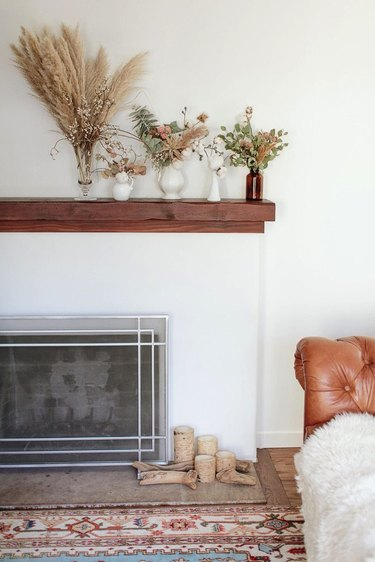 vases full of dried foliage lined up on a wood mantel