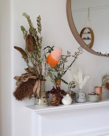 vases full of dried foliage lined up on a white mantel