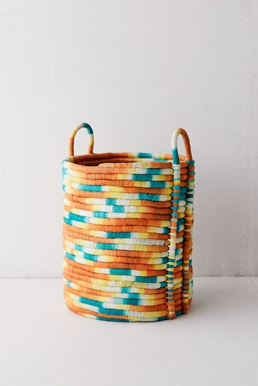 orange, blue, yellow, and white woven basket with handles