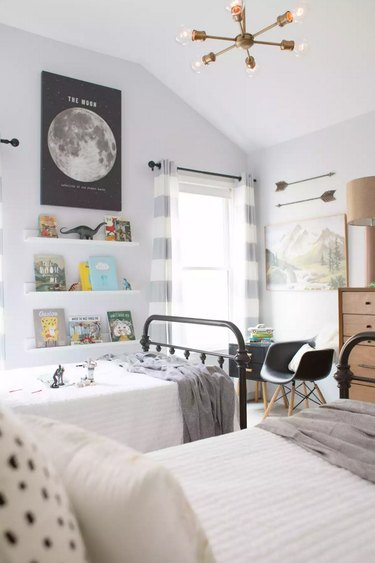 Midcentury kids' bedroom idea with Sputnik chandelier, white color palette, and children's books