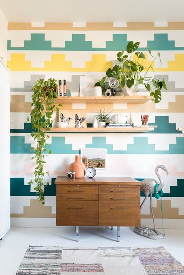 Midcentury kids' bedroom idea with multicolored wall, open shelving, and vintage drawers