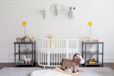 yellow nursery idea with yellow wall sconces and white crib and stuffed animals mounted to wall