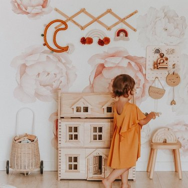 Scandinavian kids bedroom idea with wooden dollhouse and floral mural on walls