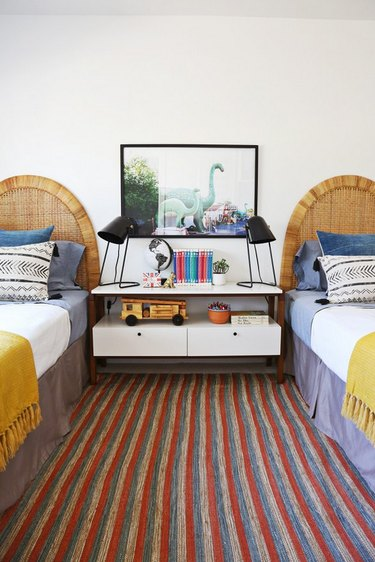 Midcentury kids' bedroom idea with matching twin beds, cane headboards, and modern table lamps