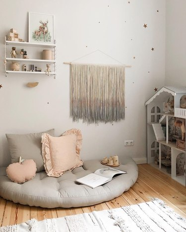 Scandinavian kids bedroom idea with gray floor cushion in kids bedroom with dollhouse and yarn wall hanging