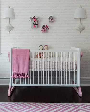 pink nursery idea with white crib and patterned wallpaper