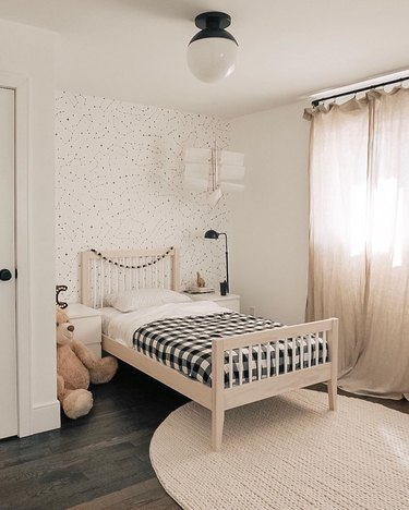 black and white Scandinavian kids bedroom idea with drapery at window and circular area rug