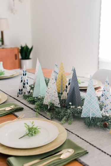 Place the paper Christmas trees on faux evergreen branches to create a centerpiece.