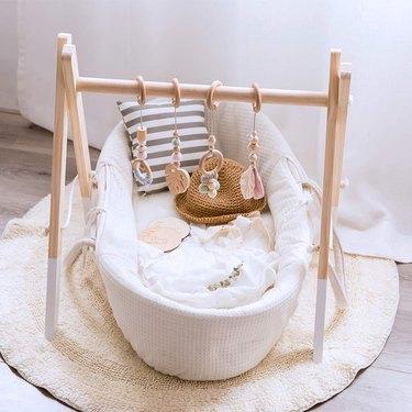 Scandinavian nursery idea with wooden baby gym on floor near window