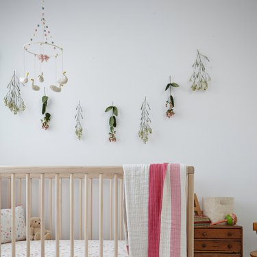 Scandinavian nursery idea with light wood crib and floral garland on wall with swan mobile hanging from ceiling