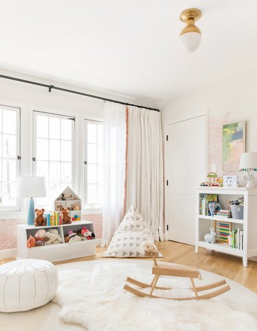 Scandinavian nursery idea with wood rocking horse on top of layered rugs in front of large windows
