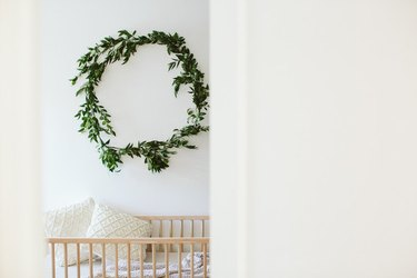 Scandinavian nursery idea with light wood crib and eucalyptus wreath hanging on wall above