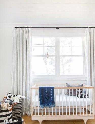 Scandinavian nursery idea with crib in front of window