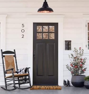 front porch with shiplap style wall and black door