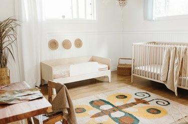 Minimal bohemian baby nursery idea with vintage butterfly rug