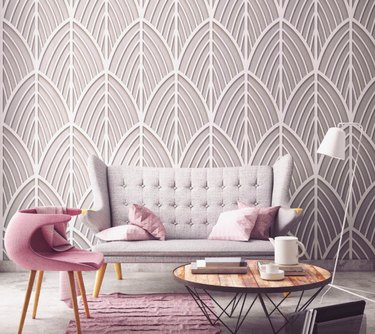 living room space with gray couch and pink chair and geometric patterned wall