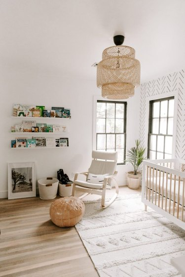 Scandinavian nursery idea with IKEA pendant and open shelving on walls with wallpaper accent wall