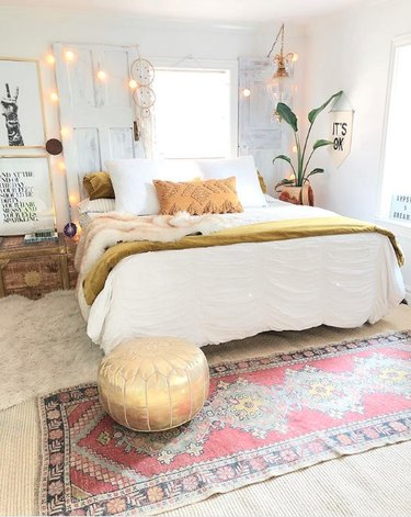 Bohemian bedroom with multiple rugs, white globe string lights, plants, and gold pouf