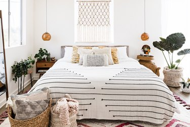 bedroom furniture idea with woven baskets and wall hanging above bed with hanging pendants
