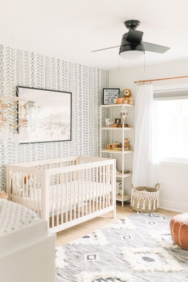 bohemian baby nursery idea with mudcloth-inspired wallpaper and ceiling fan